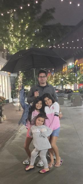 Millie's husband and girls under umbrella